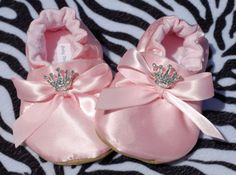 She will be your little couture baby in these sweet princess shoes! A lovely soft satiny pink ballerina shoe for your princess. Top of bows are adorned with crystal princess crowns. Shoes are lined in pale pink 100% cotton flannel and tied with a precious pink satin bow. Faux suede soles complete the shoes. Wow everyone at the baby shower, or spoil the special baby girl in your life.