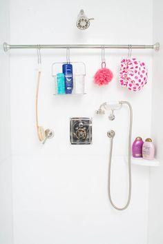 Ou então pendure um varão de cortina adicional no banheiro e use ganchos em S para colocar as coisas. | 23 maneiras inteligentes de organizar seu apartamento pequeno