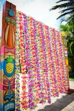 luau party entrance made of leis or a great pool party photo backdrop. water themed party decor ideas