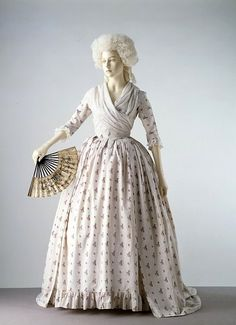 In the 1770s and 1780s printed cotton fabrics began to replace silk in popularity for women's gowns. The material of this gown has a dotted ground and is printed in a repeating pattern of floral sprays. The gown has a fitted back and open front below the waist, revealing a petticoat of the same fabric. The lack of decoration and use of cotton instead of silk indicates that this gown was probably worn during summer afternoons for card games and tea parties, rather than for evening dress.