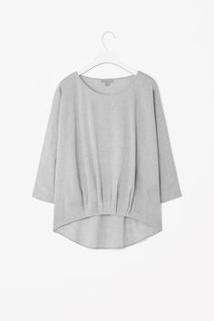 Made from fine cotton chambray with a melange quality, this top has a softly pleated hemline. An easy, relaxed style, it is a loose fit with a wide round neckline, 3/4 sleeves and is slightly longer at the back.