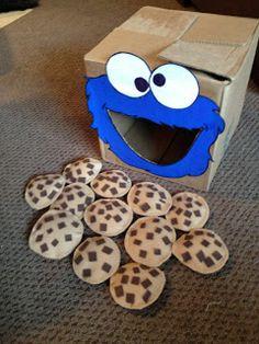 """Cookie Monster. Una caja y """"galletas"""" de tela rellenas de lentejas o frijoles. Estas galletas, a cambio de estar cosidas, están hechas de fieltro de 2 tonos y pegadas con la pistola de silicona caliente."""