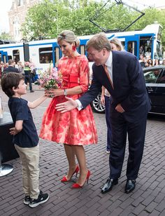 King Willem-Alexander and Queen Maxima of The Netherlands are offered flowers by a boy before attending the opening of Holland Festival on June 4 2016 in Amsterdam Netherlands.