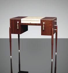 """French Art Deco: """"Poudreuse fuseaux"""" par Emile-Jacques Ruhlmann, en amarante, le plateau gainé au centre d'un tapis en galuchat à croisillons en ivoire et encadré d'ivoire, le pourtour du plateau souligné d'une frise de denticules en ivoire ; ouvrant en façade par un tiroir en ceinture et deux portes dégageant des casiers et trois tiroirs sur le côté droit du meuble ouvrant par des boutons d'ivoire ; quatre pieds en décrochement mouluré à gradins, terminés par des sabots d'ivoire. Vers 1925."""