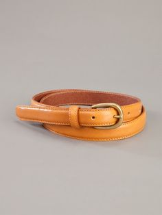 Tan leather skinny belt from Labour of Love featuring a brass tone buckle fastening.