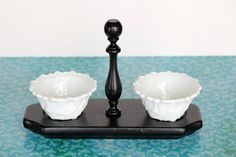 Nothing beats a classic combo like black and white. Itll never go out of style. This 3 piece black and white serving set is just that. It includes two matching white decorative bowls that sit atop a black wood holder. Its sure to become your go to condiment holder at parties and family get-togethers for years to come.  The wood part of this vintage serving set was in rough shape, so it was given a new coat of black gloss paint. The wood holder did have some wear that is still visible even…