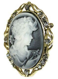 So regal and refined, our Victorian Cameo Brooch in Gray will transport you back to the days of calling cards and horse drawn carriages. A real beauty for the 19th century socialite.Featuring an ivory profile cast with a gray hue, the oval cameo is framed with gold-tone flourishes and faux gray colored stones. Ideal to wear on your evening wrap or lacy jabot. Measures 1 3/4-inches tall and 1 1/5-inches wide. Imported.