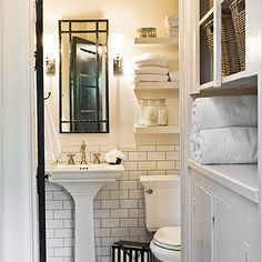 "Haskell Harris installed the tile in the small cottage bath. ""It's really simple because it comes in sheets. The dark gray grout makes it look older, and it's easy to clean.""photo: Charles Walton IV / styling Todd Childs. The medicine cabinet is a crafts store mirror, lacquered black and hung over a niche in the wall. Its thin profile allows for two sconces."