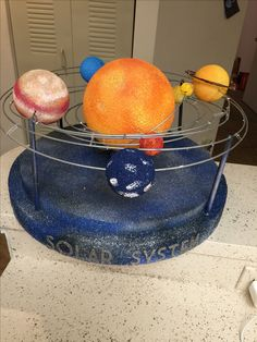 """3D Solar System  All items found at Michael's Craft store. Styrofoam Balls. Wire used from Wreath wire. Separated wires from wreath then Spray painted it Silver. Tied the wires together with clear hair elastic ties. Then glitter sticker letters on bottom to spell out """"solar system"""""""