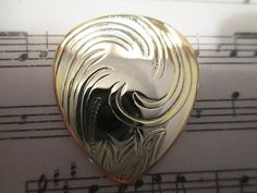 Silver and Brass Swirl Guitar Pick....  Click on the picture to buy!