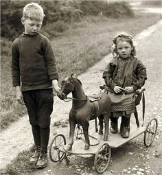 Vintage photo of children riding their toy horse