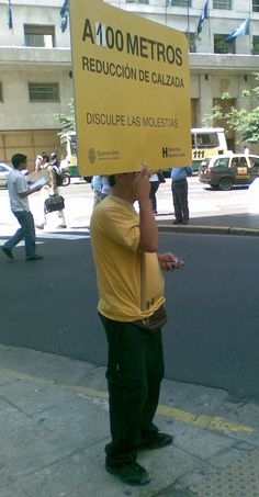 """""""road narrows in 100 meters"""". It seems like paying someone to hold the sign is cheaper than  buying a steel pole. Buenos Aires downtown."""