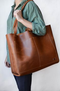 Large leather tote is perfect for work or travel! An original Nomad design, this bag features four pockets (3 exterior, and one interior), a double snap adjustable closure and a wrapped shoulder strap for added comfort. Largest pocket holds a 13.3 laptop. Smaller interior pocket sized to accommodate full-size a iPad. Perfect Carry-on size for easy air travel. Great briefcase or diaper bag alternative. Featured leather: Chestnut Measurements: Top opening- 20 Depth- 5 1 Large exterior… Gigi Bags, Leather Bags Handmade, Handmade Bags, Leather Craft, Leather Handbags, Leather Totes, Weekender Tote, Everyday Bag, Leather Projects