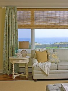 In this casually elegant living room, designer Allison Rejeanne uses the home's surroundings as inspiration to create the ultimate spot for rest and relaxation. The aqua- and sandy-hued palette is the perfect balance of color and neutrality, while also bringing in natural sea-inspired tones. To pull in more of that beachy feel, Allison adds colored glass bottles, a glass ball lamp wrapped in fisherman's netting, coral pieces and distressed furnishings.
