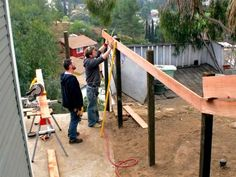 A redwood fence is built on an angle to lend privacy to a sloping backyard on HGTV.com.