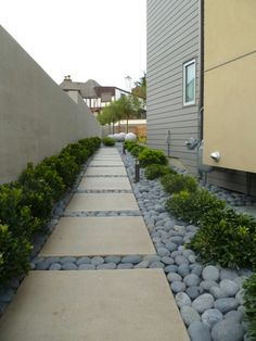 Walkway with river stones and pavers flanked with boxwoods