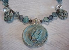 Ceramic pendant and charms by Sheri Mallery of SlinginMud.etsy.com.