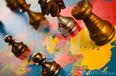 Closeup of chess pieces on a world map.