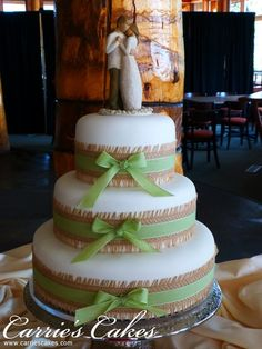 Burlap and ribbon accent a white cake with a Willow Tree cake topper.