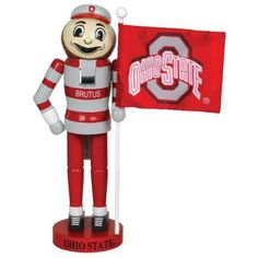 Brutus Buckeye makes a fun nutcracker for your holiday decor. Painted in red and gray, he's holding a flag with the Ohio State logo on it. Take your school pride to the next festive level with this fun piece. Michigan State Mascot, Ohio State Decor, Ohio State Wreath, Ohio State Logo, Ohio State University, Oregon Ducks Football, Ohio State Football, Ohio State Buckeyes