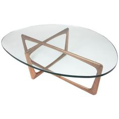 The large IonDesign Vlad Coffee Table will add retro elegance to any modern living space. The top is a thick, asymmetrical slab of clear tempered glass, which allows you to see the beauty and warmth of the wood base from any angle. Crafted out of solid American walnut and coated in a clear finish, the base will retain its warmth and smoothness--and sculptural distinction--for many years to come.