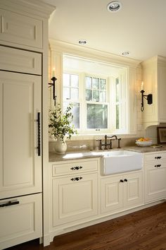 Like the cabinet hardware and colour with the darker floor. Love the candle sconces above sink and the farm sink.