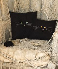 ThanksHalloween Crafts: Black Cat Pillows  Turn ordinary black pillows into creative Holiday decorations with crystal buttons and just two strands of floss Skill Level: Beginner Materials: Hand sewing needles; black thread; 12-inch black or pink button; black pillow (about 12 inches across in any fabric as desired); two 12-inch crystal buttons; white embroidery floss. Directions: 1. Thread a long needle with black thread; sew the 12-inch button to the center of the pillow,