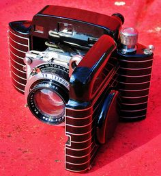 """With its beautiful Art Deco styling by Walter Dorwin Teague, the Kodak Bantam Special is considered by many to be one of the most beautiful camera designs ever. The Bantam Special's clam shell styling enabled it to become a truly pocketable, and practical carry everywhere camera. It measures only 3 3/16"""" x 4 13/16"""" x 1 13/16"""" deep and weighs in at a petite 17oz. Its body is remarkably elegant, having a beautiful black enamel finish with machined aluminum die cast body."""