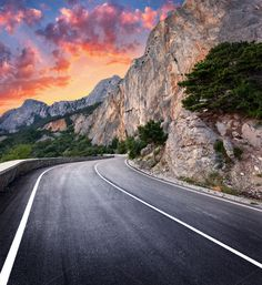 Colorful landscape with beautiful winding mountain road with a perfect asphalt with high rocks, amazing sky at sunset in summer. Asphalt Road, City Car, Female Art, Country Roads, Sky, Mountains, Sunset, Landscape, Travel