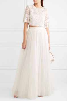 Two Piece Wedding Dress: This romantic, sophisticated two piece wedding dress from Needle and Thread is made up by pairing an ivory tulle wedding maxi skirt featuring a grosgrain waist with the rosette embellished tulle top. The embroidered, loose, pale blush, shimmery box top is a fantastic match up!