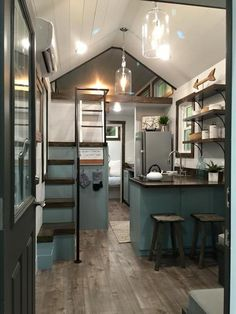 Driftwood Homes debuted Sweetgrass at the Sevierville, TN tiny home show. The interior of this 24' tiny house is a beautiful blend of white walls, blue cabinets, and dark stained wood.