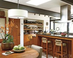 A Faber vent hood hangs above concrete countertops in the kitchen;    the cabinetry is made of oiled teak, the stools are vintage, and the teak table    and glass-paneled Børge Mogensen cabinet are from the '50s.    - ELLEDecor.com