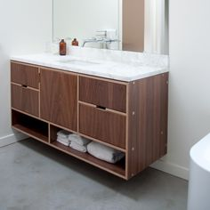 Walnut floating bathroom sink vanity with marble countertop and undermount sink and mirror faucet. Euro plywood cabinetry by Kerf Design. kerfdesign.com