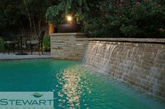 A wall edge on a pool can not only be a lovely water feature, but it can help divide your yard into sections in a subtle way. #StewartLandDesigns