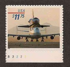 The space shuttle is lifting off on the back of a transport plan in this postage stamp picture depicting one of the many space themed express and priority mail stamps issued by the US Postal Service.