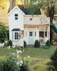 White two-story playhouse with an adorable blue door // Playhouse