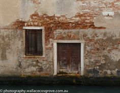 Venice door - A door and a window in a crumbling brick wall by a Venice canal.