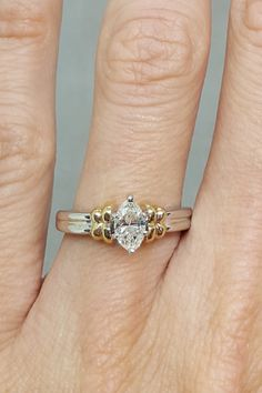 This ring is a prime example of how each engagement ring in the 1990s was unique. The marquise-cut, 0.6 carat solitaire diamond is bordered by a yellow gold knot on the band. #vintagerings #vintageengagementrings #engagementrings #southernliving