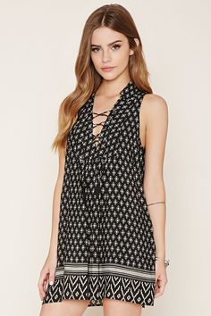 This sleeveless woven mini dress features an allover geo print, a Southwestern print along the hem, a tasseled lace-up neckline, and a basic collar.