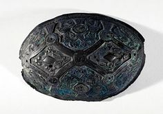 Bronze Viking Brooch  Shetland Museum  SCRAN ID No 000-000-000-331-C  A single shell brooch decorated with diamond-shaped panels of zoomorphic motifs, separated by small, raised bands on which some lighter coloured metal, possible gilding, can be detected. Nine slightly raised bases with holes through their centres indicate accommodation of decorative bosses, but these are missing...'.