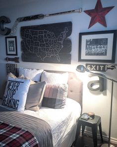 Love this Rustic Teen Boy's Room and Gallery Wall! Map on wood is from World Market, plaid blanket is Pottery Barn Kids, wall color is Sherwin Williams On the Rocks, lamp is from Lowe's, stool is from Hobby Lobby, black and white sports photos are of his grandfathers, Never Stop Dreaming pillow is from Hobby Lobby, signed hockey stick