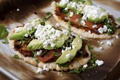 Huaraches Topped with Chorizo Refried Beans, Tomatoes, Avocados, and Goat Cheese