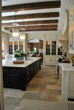 the beams in this kitchen are amazing along with the black island and white cabinets