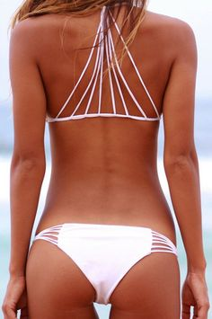 29e4b42e96 Get ready for the summer in this caged strappy white bikini set. It  features a halter neck with interlocking string design at the back.