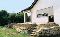 hohe Terrasse mit Natursteinmauer