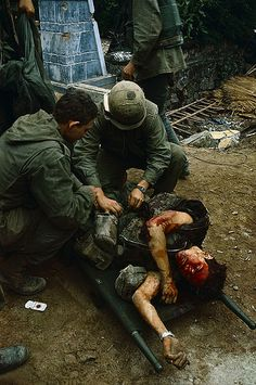 February 1968, Hue, South Vietnam --- U. S. Marine medics treat a wounded fellow Marine whose face is almost completely covered with blood. --- Image by © Bettmann/CORBIS