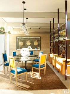 In the dining room, original Raak globe pendants hover above Napoléon III painted side chairs from Lucullus Antiques and a Saarinen table. A photograph by Jungjin Lee hangs on a wall clad in a Phillip Jeffries grass cloth, while an Eva Hild sculpture rests on the dining table and Peter Lane ceramic sculptures are showcased on a George Nelson storage system original to the house.