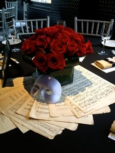 Our Phantom of the Opera theme tables started with a red rose arrangement (Ariston Flowers) and incorporated the iconic mask, handheld mirrors and antique music sheets from Love Dove Trading Company (Etsy)