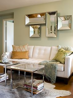 Love the collection of mirrors in this living room space.  While creating visual interest these mirrors also open up the space by reflecting the light around the room.  Elegance achieved with a tailored white sofa, glass and chrome tables, cow-hide rug and lovely pale green walls. #mirrors http://www.aftershocksinteriordecorating.com