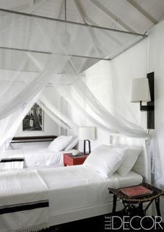 French decorator Christian Liaigre built a trio of bungalows above the coast of Saint Lucia for friends. In the all-white guesthouse, mosquito netting is draped over twin beds dressed with D. Porthault linens.